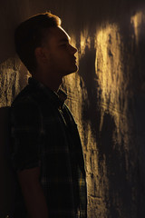 Contrast silhouette of man standing near wall in bright sun ligh