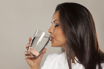 Woman doctor drinking a water from a glass
