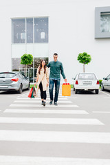 Woman and man crossing the street with shopping bags