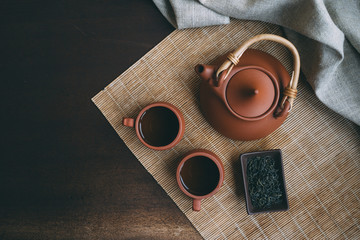 Chinese Tea Ceremony. Brown ceramic teapot and brown tea cup .Green tea on bamboo mat on aged wooden table. Top view.