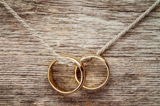 Wedding rings hanging on rope.