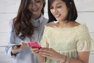 Two young women looking at a smartphone together