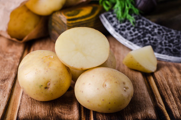 Fresh young potatoes on wooden background. Selective focus