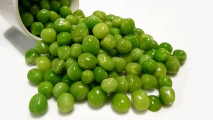 Isolated healthy fresh green peas scattered on white background