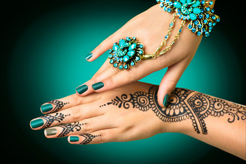 Woman's hands with mehndi tattoo. Hands of Indian bride girl with black henna tattoos
