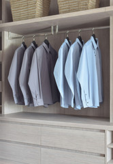Light blue and grey shirts in light wooden wardrobe