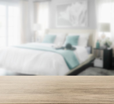 wooden table top with blur of cozy bedroom interior with white and green pillows on bed