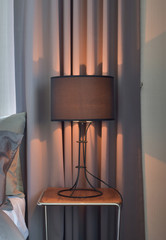 Black shade reading lamp next to bed
