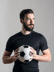 Confident serious football or soccer player intense portrait looking at light source over gray studio background.