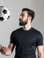 Side view of bearded young football or soccer player throwing ball over gray studio background.