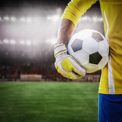 close up goalkeeper holding soccer ball