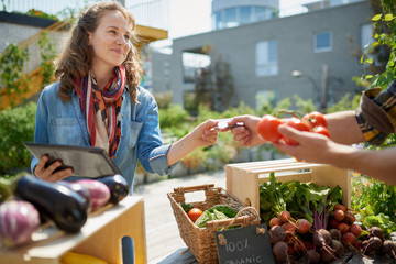 Friendly woman tending an organic vegetable stall at a farmer's market and selling fresh vegetables from the rooftop garden