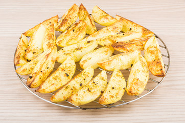 Pieces of baked potatoes on grill