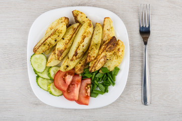 Pieces of baked potatoes with slices of tomatoes and cucumbers