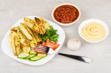 Pieces of baked potatoes with slices of tomatoes, cucumbers