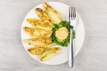 Slices of baked potatoes with mayonnaise and leek in plate