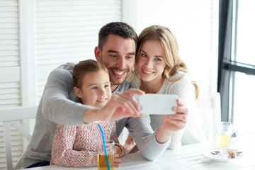 happy family taking selfie at restaurant