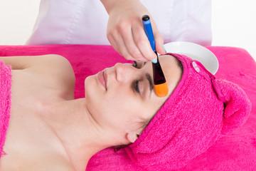 Girl putting a facial peel off mask on gray. Peeling