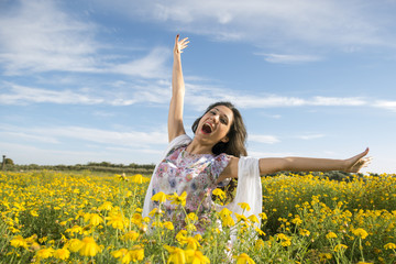 Young happy woman standing in yellow daises field
