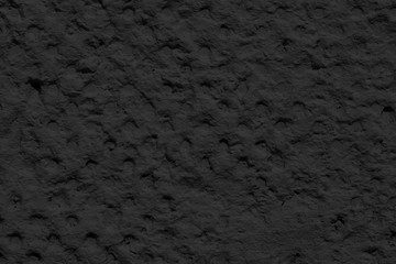 Cement or plaster wall. Black background.