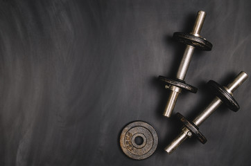 Iron dumbbells on a black chalkboard seen from above. Photo taken from above, top view. Conceptual image background for sport or fitness advertising. Horizontal image.