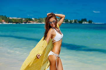 Young pretty woman in summer near the sea and blue sky in yellow
