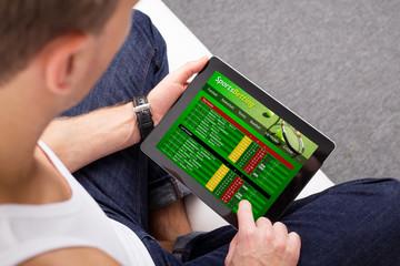 Man using sports betting app on tablet