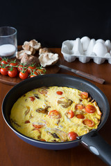 Frittata with cherry tomatoes and shiitake mushrooms. Selective focus.