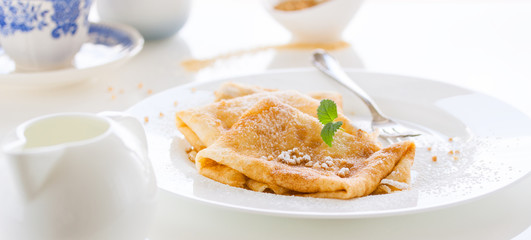 French crepes or pancakes with sugar powder, nuts and fresh mint on a white plate on a white background for breakfast, closeup