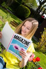 Junge Frau liest im Garten Zeitschrift