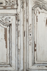 Close-up of keyhole ancient white commode bureau furniture with paint peeled off