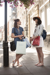 Two stylish women with shopping bags chatting on city street