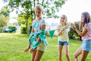 Girls wrapping friend up in bunting