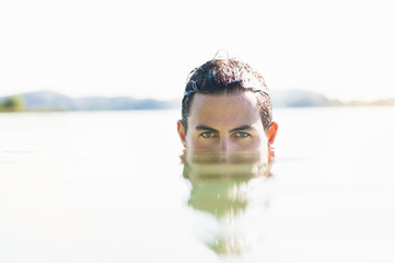 Portrait of young man with face submerged in lake, Woerthsee, Bavaria, Germany