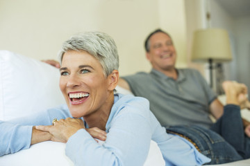 Mature couple laughing and relaxing on sofa