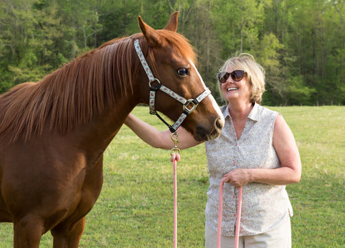 older Arabian brown and white mature horse in pasture with  happy woman petting mane