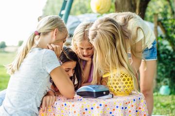 Girls crowding around instant film camera at summer garden party