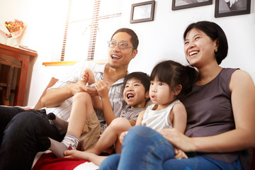 Young, modern Chinese family of parents and two young children sitting on sofa watching television together at home