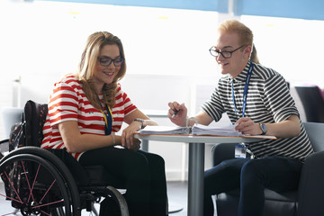 Teacher and female student in wheelchair having classroom tutorial