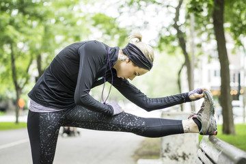 A young blonde woman exercising in park