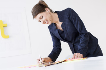 Mature woman wearing business attire writing on paperwork, looking down smiling