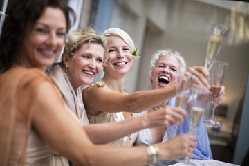 Elegant mature women toasting in urban garden