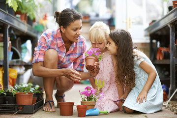 Mid adult woman and two girls smelling flower pots in greenhouse