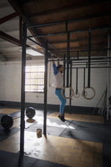 Crossfitter doing pull ups in gym