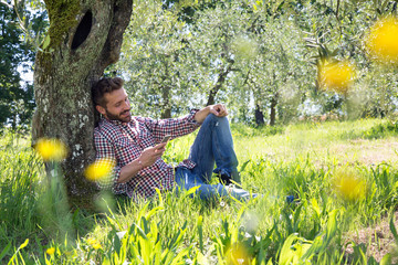 Young man sitting leaning against tree using smartphone looking down smiling