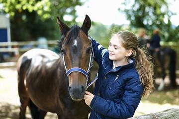 Girl putting halter onto horse