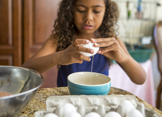 Girl cracking eggs into bowl looking down