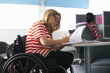 Teenage girl in wheelchair writing up notes in class