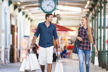 Young couple carrying shopping bags in arcade