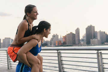 Two friends giving a piggy back after exercising together in running clothes next to river